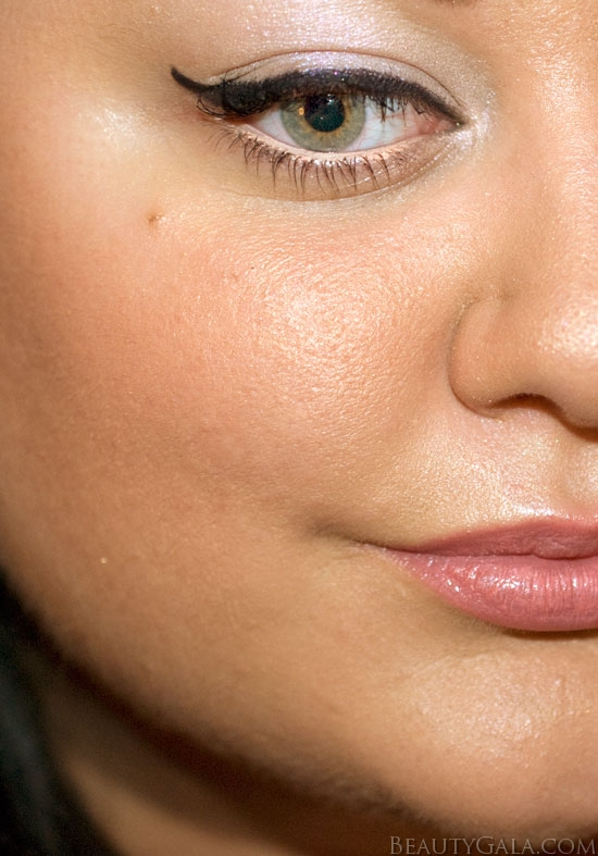 The cheekbones are contoured, bronzed, and topped with pink blush. The eyes are feline-like. The skin is glowing and luminous.